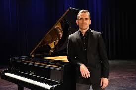 Zdjęcie Adama Niedzielin, na tle fortepianu.